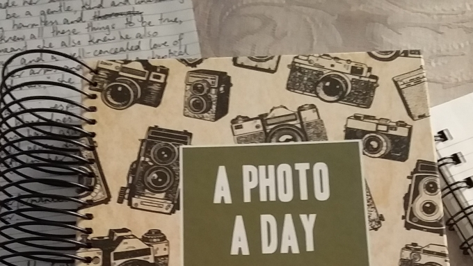 "A page with handwritten notes lies next to an album with the title ""A Photo A Day"" and the corner of an open notebook."