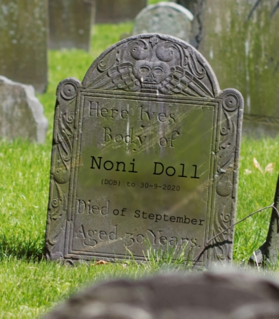 "An old grave in a green cemetery. Poorly photoshopped on are the words: ""Here lyes [sic] the body of Noni Doll. DOB to 30-9-2020. Died of Steptember. Aged 30 years."""